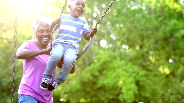 african-american grandmother pushing boy on swing - grandparent stock videos & royalty-free footage