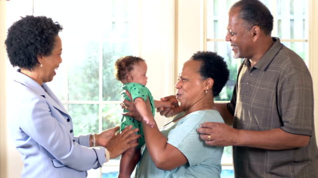 african-american grandmother showing off baby to friends - passing giving stock videos & royalty-free footage