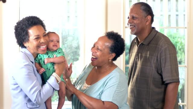 vidéos et rushes de grands-parents afro-américains exhibant le bébé à l'ami - tante