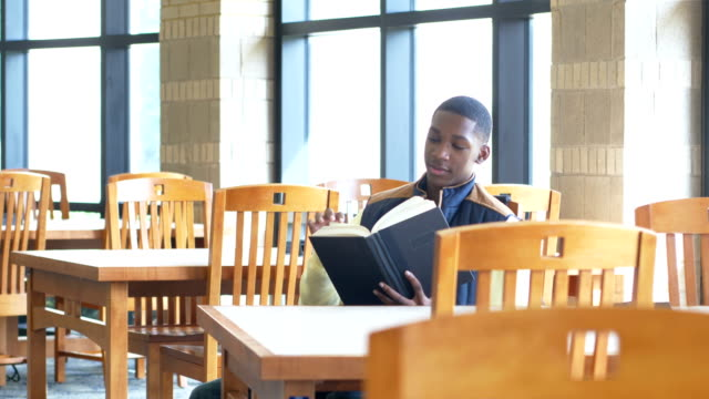 African-American high school student reading in library