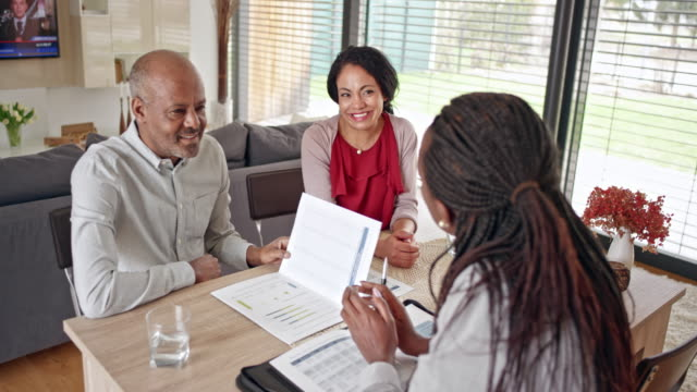 african-american insurance agent advising senior couple at home - home insurance stock videos & royalty-free footage