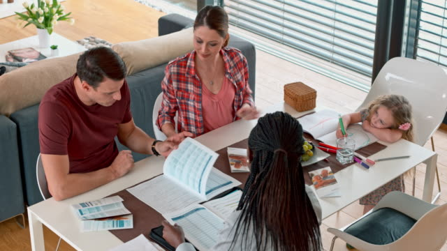African-American insurance agent meeting young family at home
