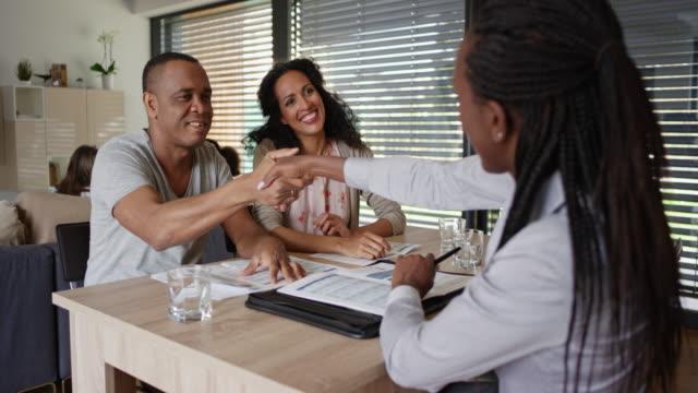 stockvideo's en b-roll-footage met afro-amerikaanse verzekeringsagent schudden handen met haar klanten op een bijeenkomst in hun huis - bank zitmeubels