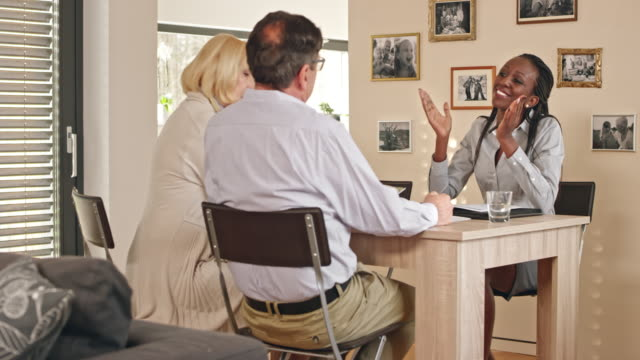 African-American insurance agent shaking hands with senior clients