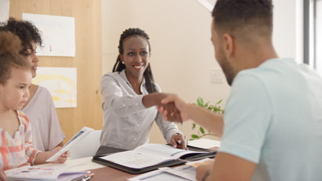 African-American insurance agent shaking hands with young family