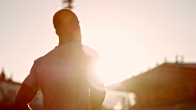 slo mo ts african-american male athlete running in stadium at sunset - tracking shot stock videos & royalty-free footage