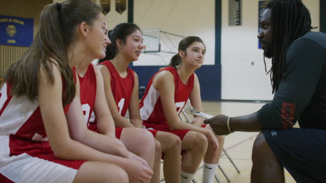African-American male coach discussing a play with the girls basketball team