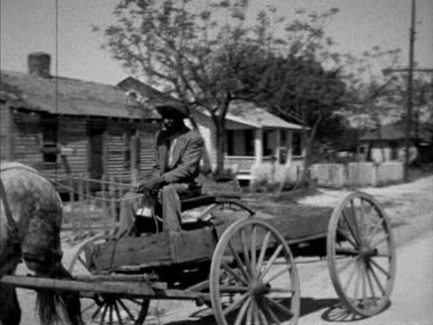 africanamerican male driving horse buggy down unpaved dirt street in low income neighborhood pan small wooden frame houses children playing... - jim crow laws stock videos & royalty-free footage