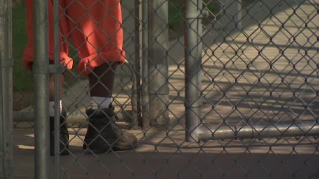 africanamerican male inmate legs in rolled up prison pants high top sneakers socks closing outer gate walking to opening inner gate walking sidewalk... - prisoner walking stock videos & royalty-free footage