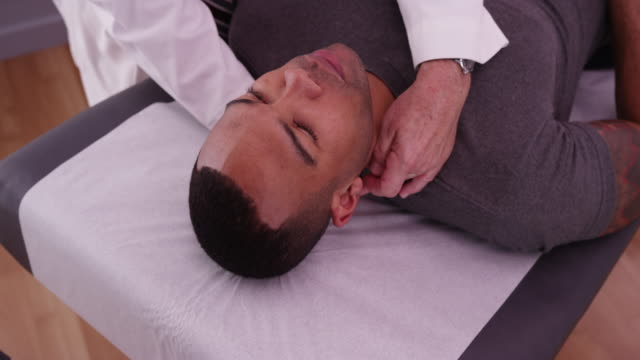vídeos de stock, filmes e b-roll de african-american male patient having neck pain examined by chiropractor - physical injury