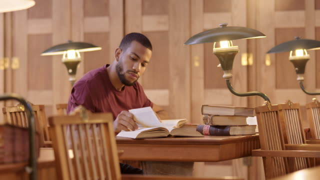 LD African-American male student reading in the library