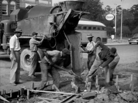 AfricanAmerican males working shoveling wet concrete in blocked off area by US Highway 1 in city pouring concrete group smoothing dirt for sidewalk...