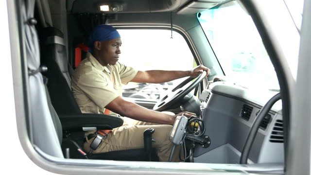 African-American man climbing into cab of semi-truck