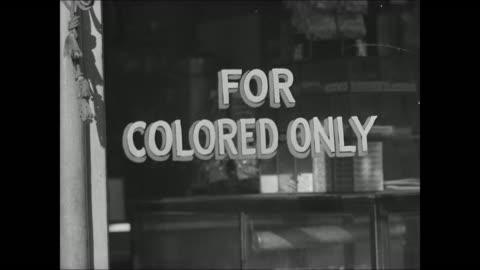 vídeos y material grabado en eventos de stock de african-american man crossing street cars shops bg. booker t. luncheon.' sign 'for colored only.' negro-americans on city streets. african-american... - separación