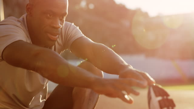 SLO MO African-American man doing stretching exercises in the stadium at sunset