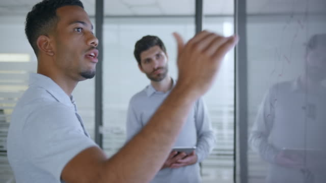 african-american man explaining a graph on the screen in meeting room to his male caucasian colleague - professione video stock e b–roll