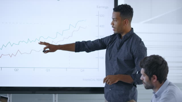 african-american man explaining the financial graph on the screen in the meeting room - explaining stock videos & royalty-free footage