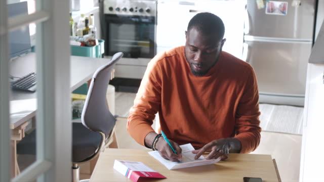 米国大統領選挙中に自宅で郵便投票を記入するアフリカ系アメリカ人男性 - voting点の映像素材/bロール