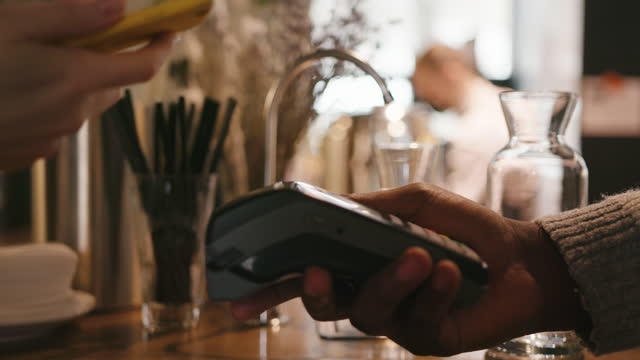 stockvideo's en b-roll-footage met afrikaans-amerikaanse mens geeft terminal aan bezoeker betalen voor bestelling - aankoop met creditcard