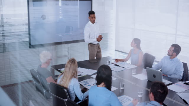 african-american man giving a presentation to his colleagues in conference room - conference table stock videos & royalty-free footage