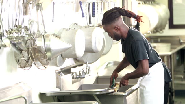 african-american man in commercial kitchen washing pots - lavastoviglie video stock e b–roll