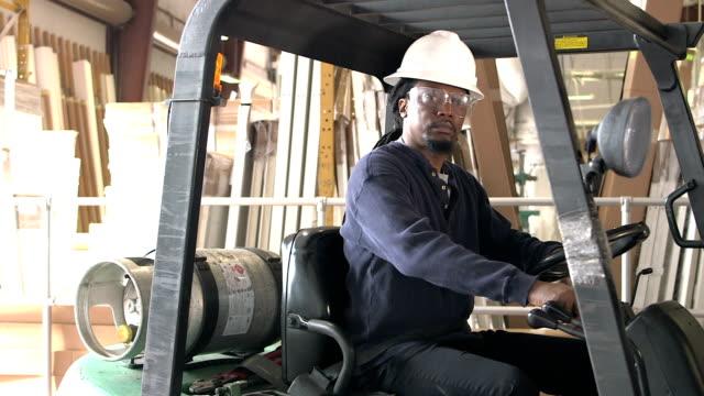 stockvideo's en b-roll-footage met afro-amerikaanse man in magazijn klimt op heftruck - veiligheidsgordel