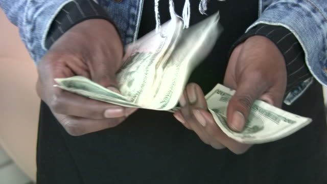African-american man male counting dollar bills by hands