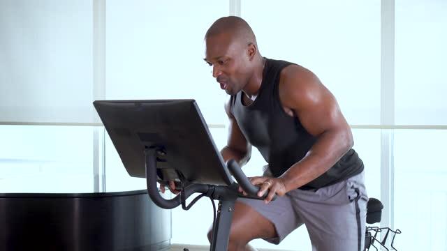 stockvideo's en b-roll-footage met african-american man on exercise bike at home - driekwartlengte
