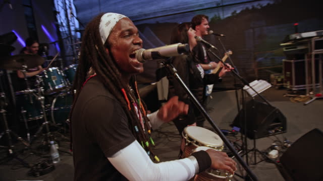 African-American man playing drums and singing in concert