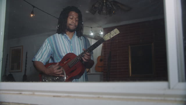 african-american man plays resonator guitar inside his home - only mid adult men stock videos & royalty-free footage