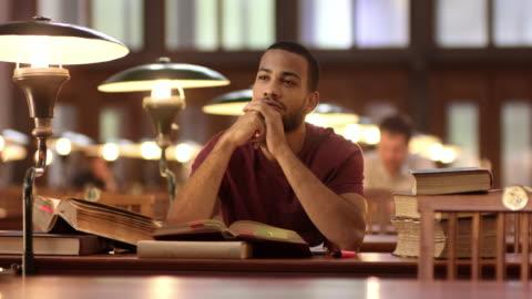 stockvideo's en b-roll-footage met ds afro-amerikaanse man peinzen in de bibliotheek - study