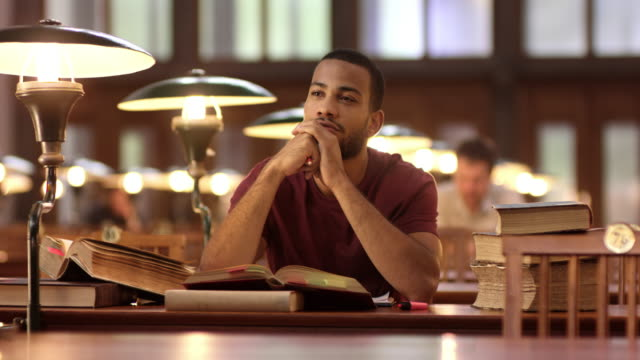 ds african-american man pondering in the library - ideas stock videos & royalty-free footage