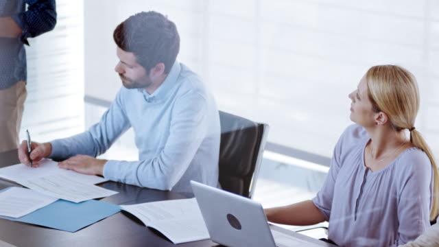 vidéos et rushes de homme afro-américain, présenter le rapport financier à ses collègues dans la salle de conférence - collègue de bureau