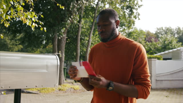 african-american man receiving mail-in voting ballot during usa presidential election - letterbox stock videos & royalty-free footage