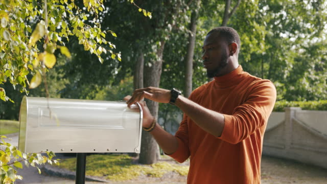 vídeos y material grabado en eventos de stock de hombre afroamericano recibiendo boleta de votación por correo durante las elecciones presidenciales de ee.uu. - un solo hombre de mediana edad