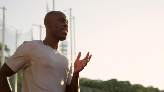 slo mo ts tu afrikanisch-amerikanischer mann läuft im stadion bei sonnenuntergang - afrikanischer abstammung stock-videos und b-roll-filmmaterial