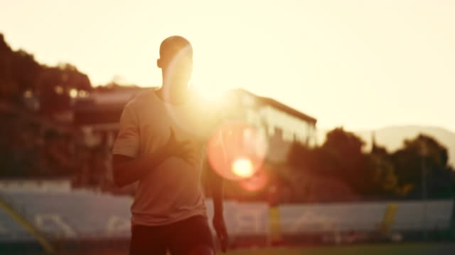 slo mo ds african-american man running in the stadium in sunset with flares - pista di atletica leggera video stock e b–roll