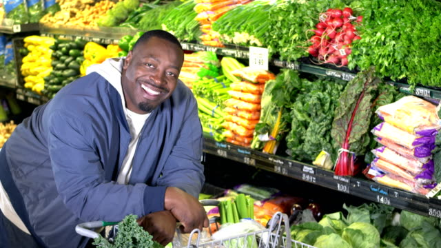 african-american man shops for groceries, produce aisle - leaning stock videos & royalty-free footage