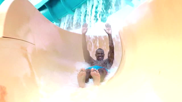 african-american man sliding down water park slide - water slide stock videos & royalty-free footage