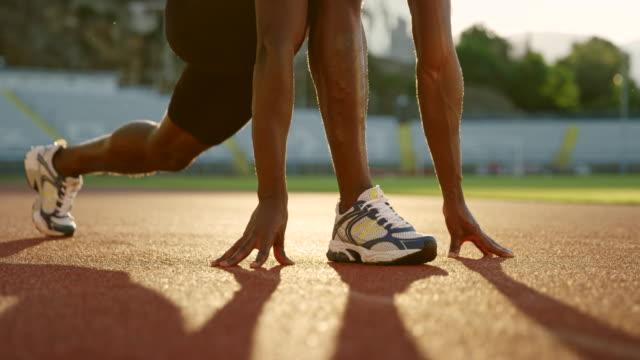 夕暮れ時スタジアムで彼の足を伸ばし slo mo ld アフリカン アメリカンの男 - ランニングトラック点の映像素材/bロール