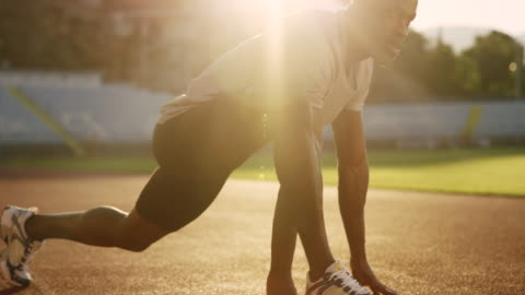 slo mo african-american man stretching in the stadium on the track in setting sun - track and field stock videos & royalty-free footage