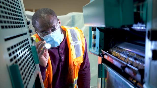 vídeos de stock, filmes e b-roll de homem afro-americano com máscara inspecionando prensa de impressão - lanterna elétrica