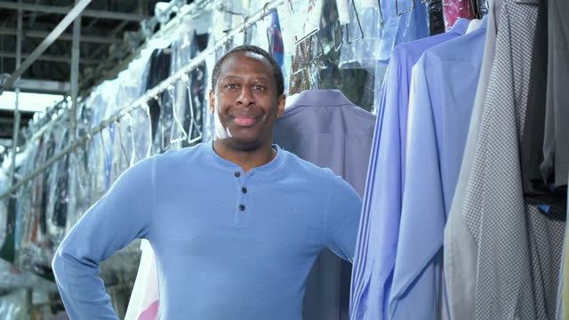 african-american man working at dry cleaners - hand on hip stock videos & royalty-free footage