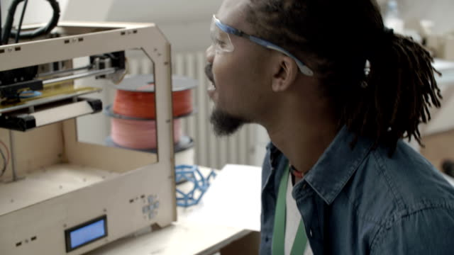 hd: african-american man working by 3d printer. - graphic design studio stock videos & royalty-free footage