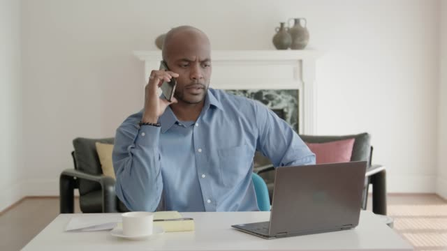African-American Man Working from Home Office and Talking on his Mobile Phone