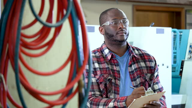 african-american man working in printing plant - plaid shirt stock videos & royalty-free footage