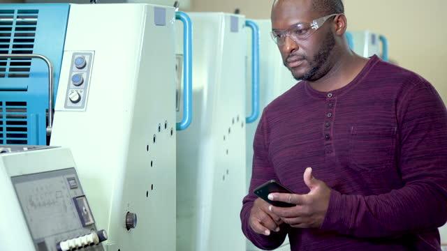 stockvideo's en b-roll-footage met afrikaans-amerikaanse mens die in drukinstallatie werkt - drukker