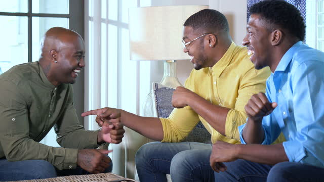 african-american men talking in living room, fist bumps - mid adult men stock videos & royalty-free footage