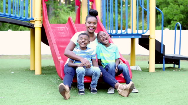 African-American mother and boys on playground