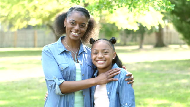 african-american mother and daughter hugging outdoors - arm around stock videos and b-roll footage
